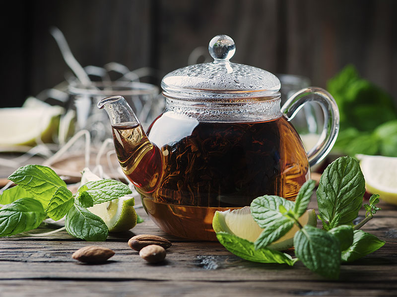 Freshly brewed tea in a kettle on a table with lemon, mint, and almonds
