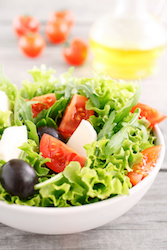 River Parishes micro-markte service of fresh summer vegetable salad with arugula, tomatoes, black olives, lettuce with mozzarella in a white deep bowl closeup on a wooden table. Focus on the tomato