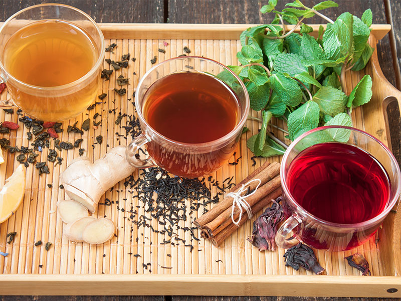Freshly brewed tea on a tray with cinnamon, mint, and ginger