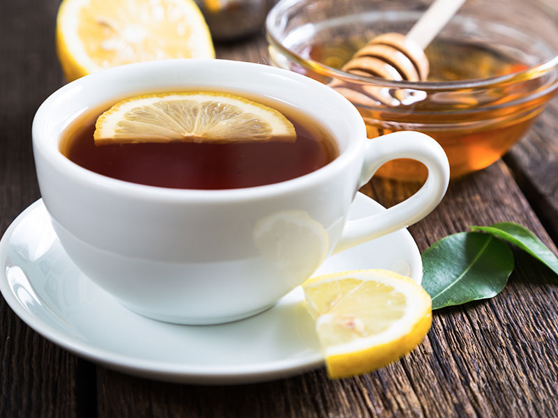 Hot tea with lemon and honey on an office desk